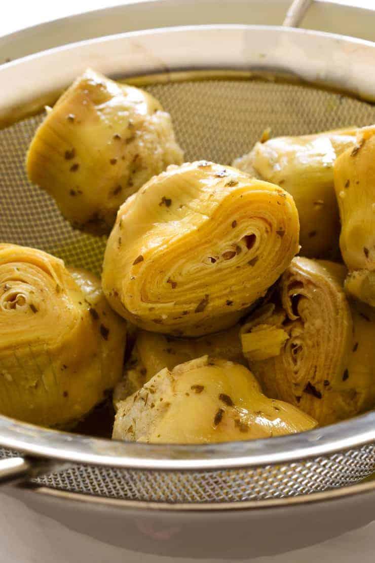 Drained artichoke hearts in a sieve.