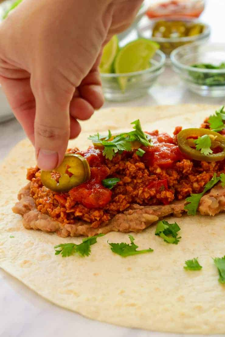 A hand dropping a jalapeño on the burrito meat filling.