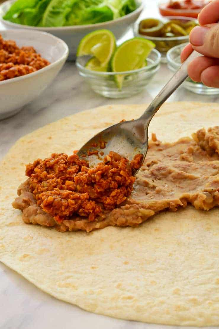 Spooning the tvp meat over the creamy beans on the tortilla.