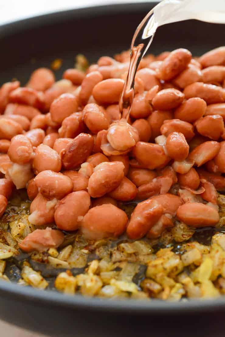 A pan of pinto beans and fried onions with water being poured over.