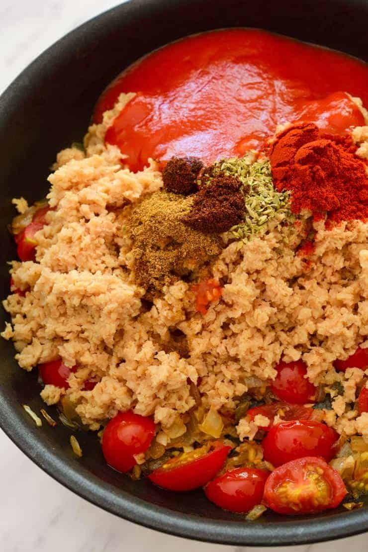 The pan of rehydrated tvp with cherry tomatoes, spices, herbs and tomato sauce before mixing.