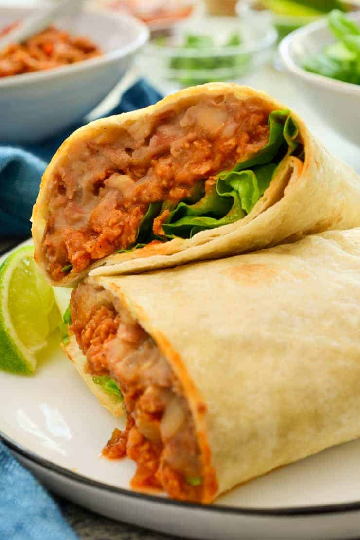 A vegan burrito cut open to expose the filling on a white plate with a lime on the side.
