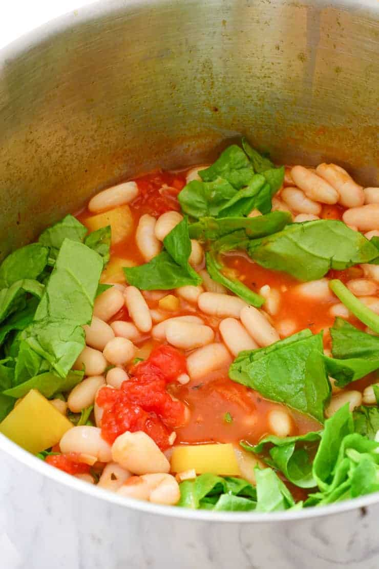 The beans and spinach in the pot with the rest of the vegan stew ingredients.