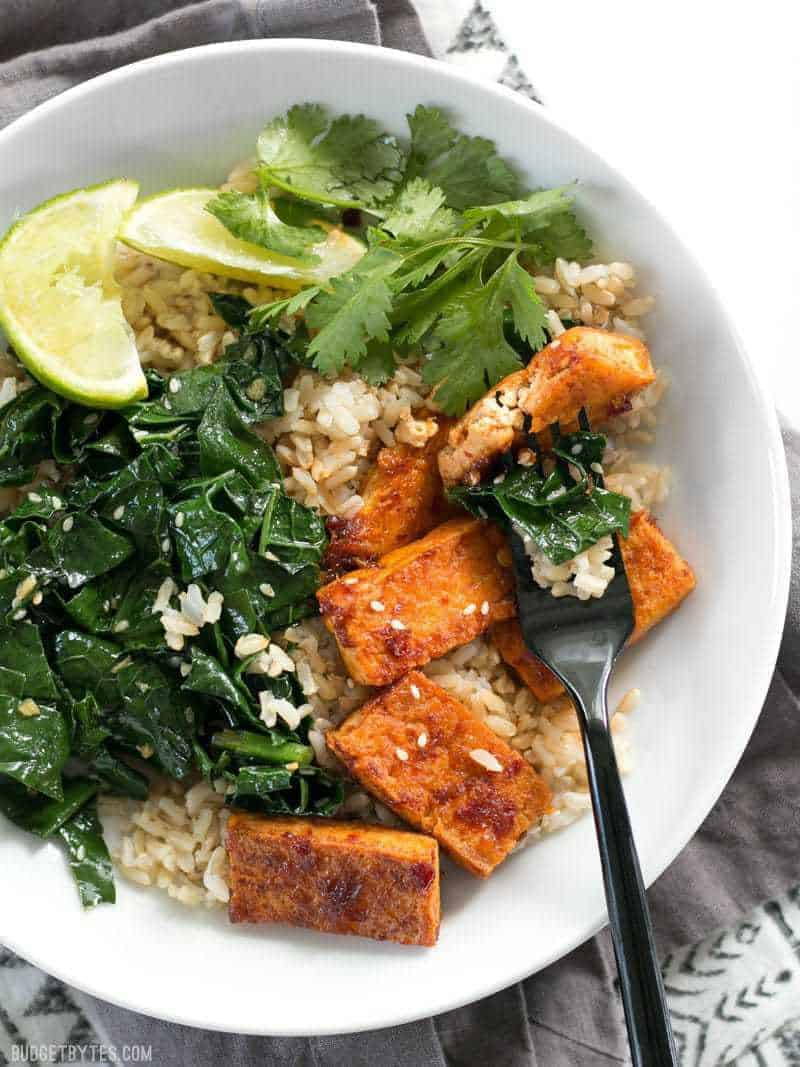 A white bowl filled with rice, greens, tofu, cilantro and lime slices.