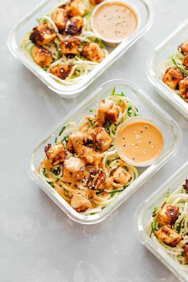 Glass containers filled with zucchini noodles and tofu with sauce drizzled over.