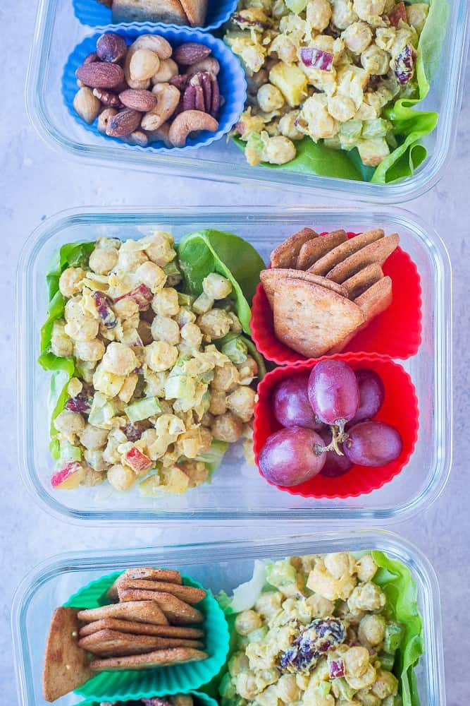 3 glass containers with leafy greens, curried chickpea salas, crackers and grapes.