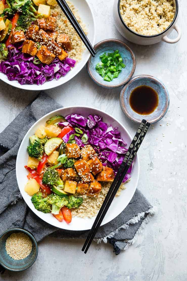 Two white bowls with rice, veggies and barbecue tofu. Small bowls of seasoning on the side.