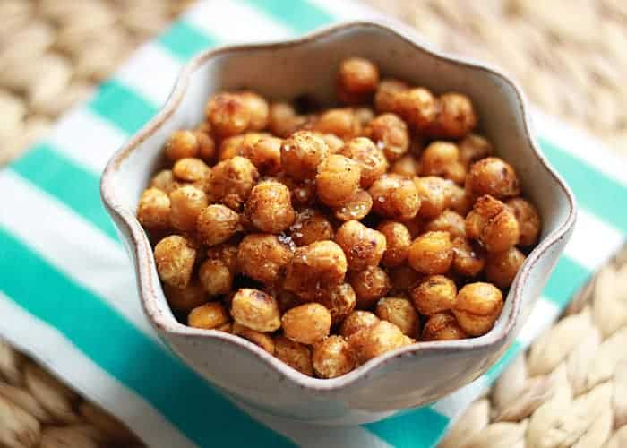 A grey bowl of roasted and seasoned chickpeas on a blue and white napkin.