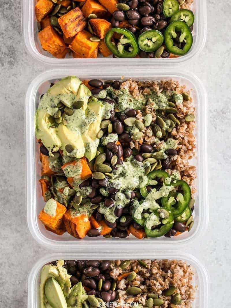 3 plastic containers with sweet potato grain bowls recipe with avocado, jalapeños, pumpkin seeds and avocado.