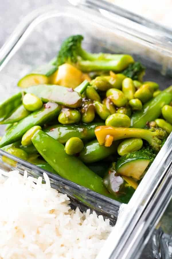 Green stir-fried veggies with teriyaki sauce and white rice in a glass storage container.