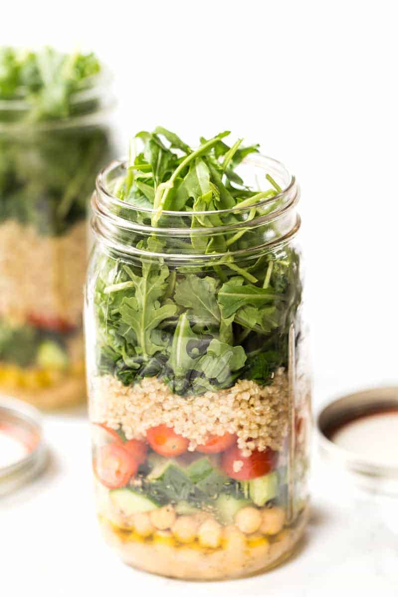 A mason jar filled with chickpeas, chopped veggies, quinoa and leafy greens.