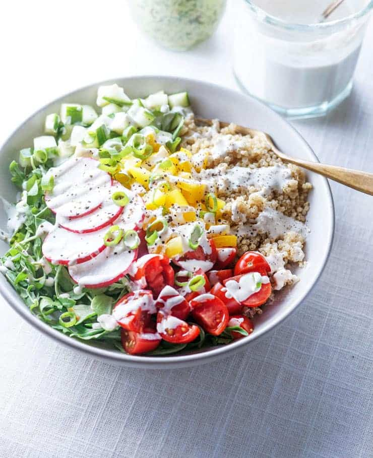 A white bowl filled with quinoa, tomatoes, leafy greens, radishes and bell peppers with tahini sauce drizzled over.