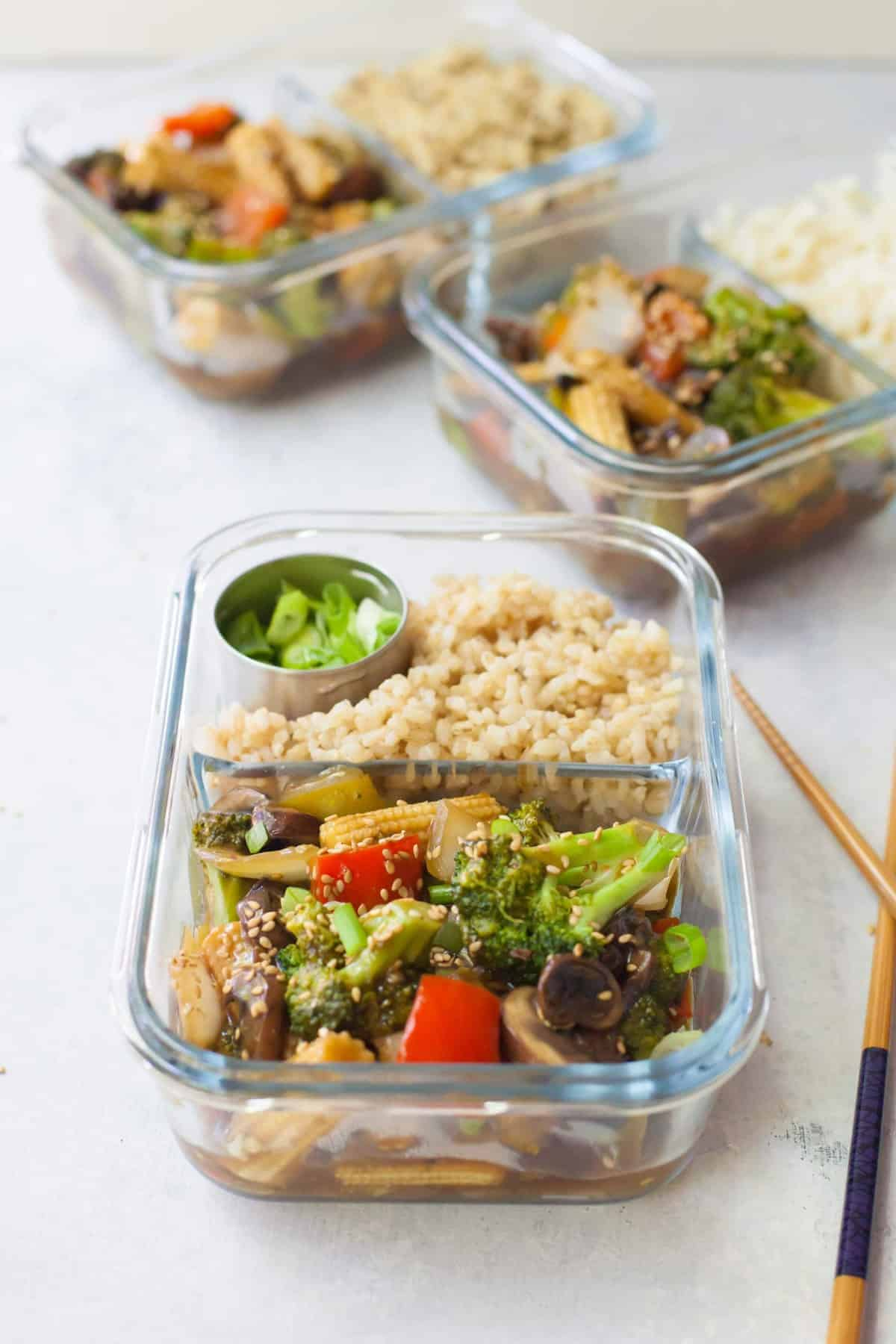 3 glass containers with veggie stir fry and rice.