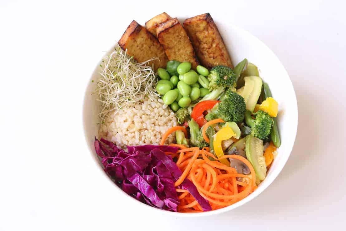 Rice, tofu, edamame and veggies in a white bowl.