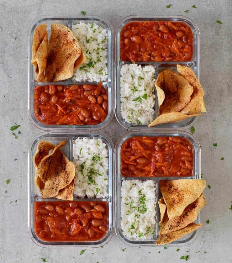 4 class containers with chili, rice and tortillas.