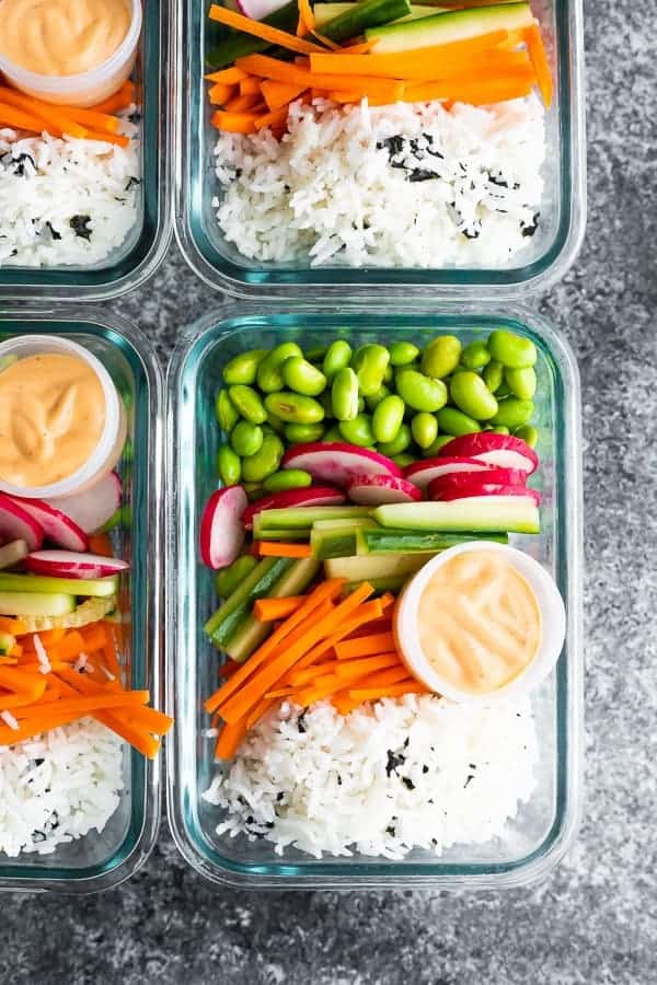 4 glass containers with rice, carrots, cucumber, radish, edamame and sauce.