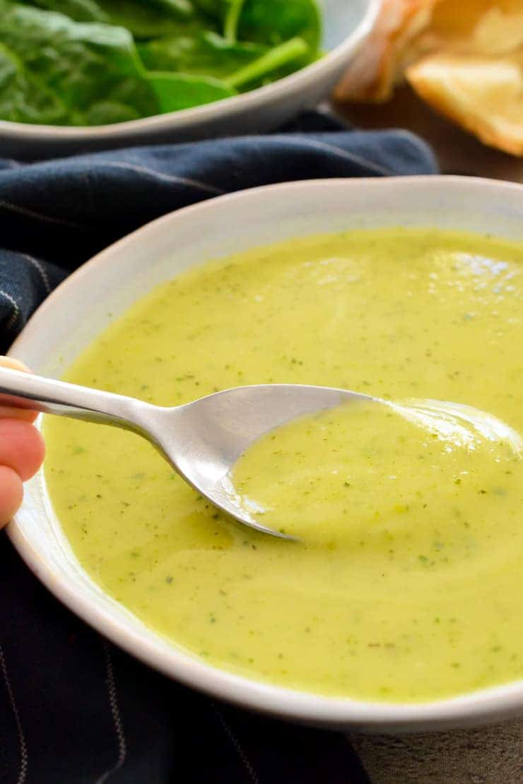 A white bowl of zucchini soup with a spoon in it.