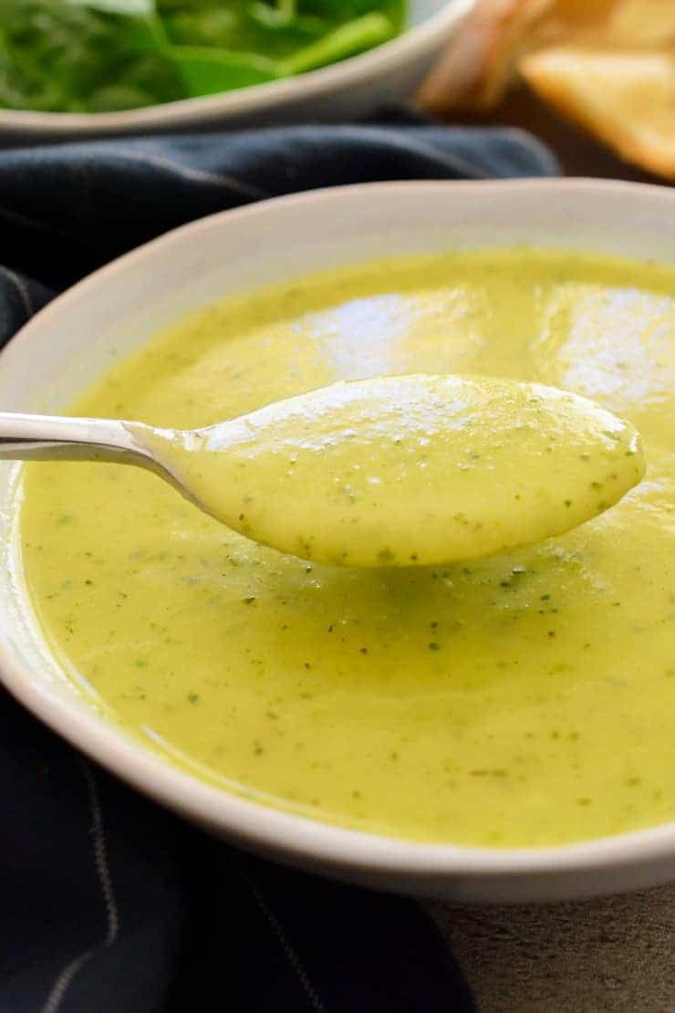 A spoonful of the soup above a white bowl of vegan zucchini soup.
