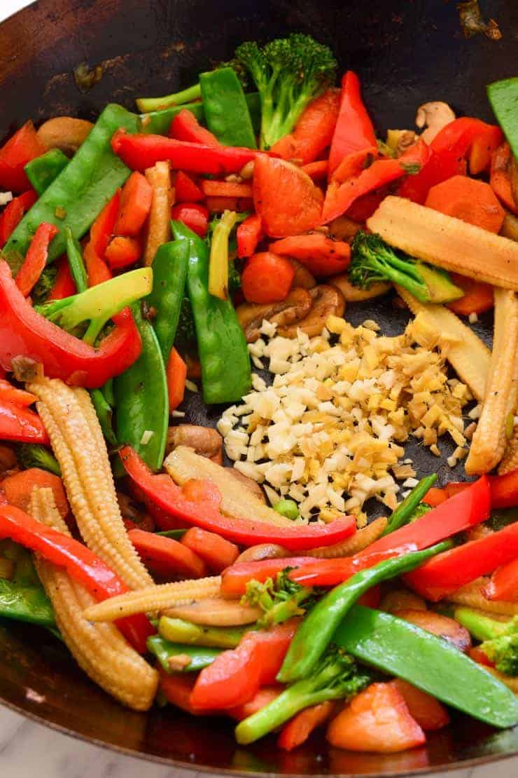 Colourful stir-fried veggies in the wok. Chopped ginger and garlic in the middle of the wok.