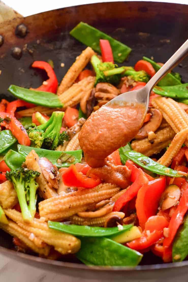 A spoon dolloping the peanut-hoisin sauce over the fried veggies in the wok.