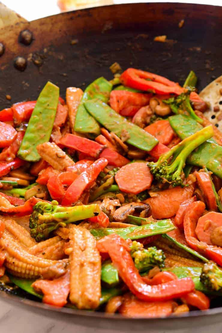 The stir fried vegetables covered in peanut sauce in the wok.
