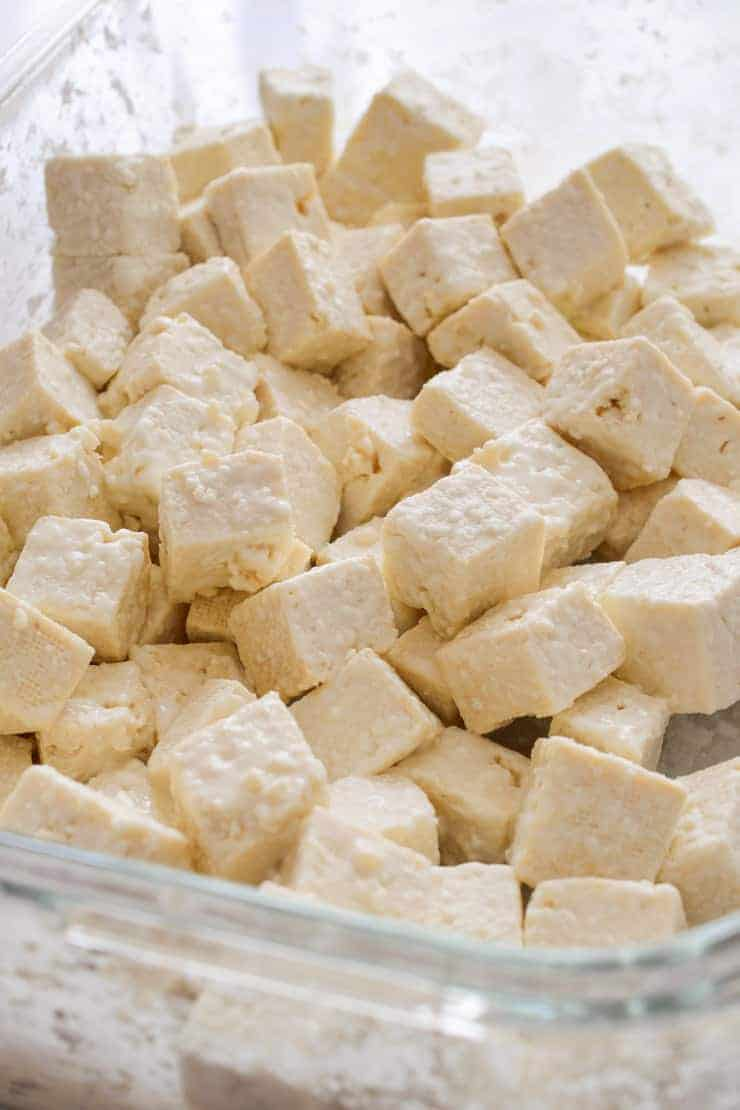 Cubes of tofu coated in cornstarch in a glass container.