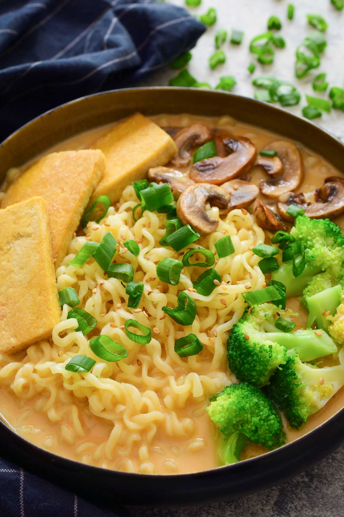 A black bowl filled with ramen, broccoli, tofu and mushrooms in a creamy vegan sesame broth. Garnished with green onions and sesame seeds.