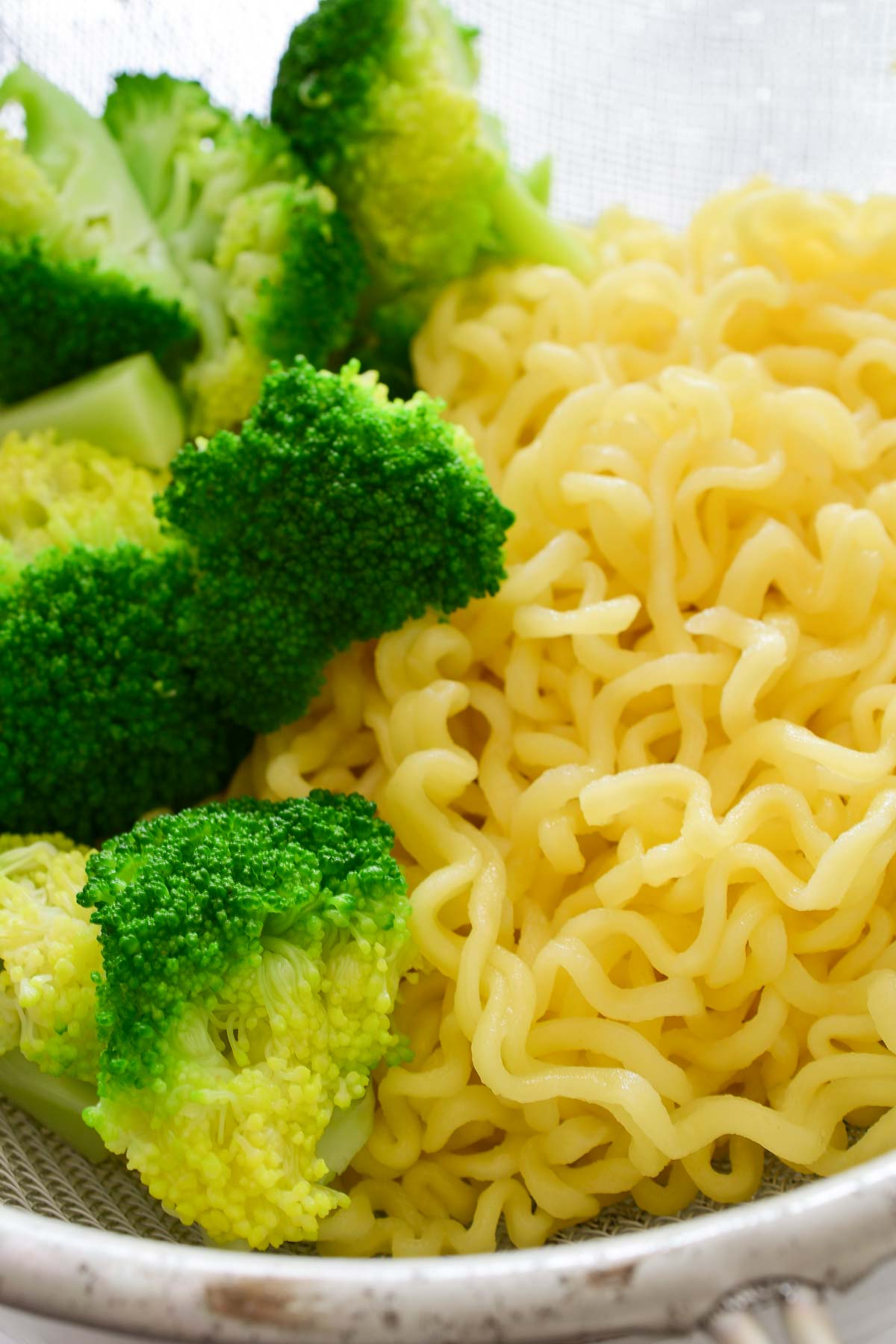 A strainer with the cooked ramen noodles and broccoli.