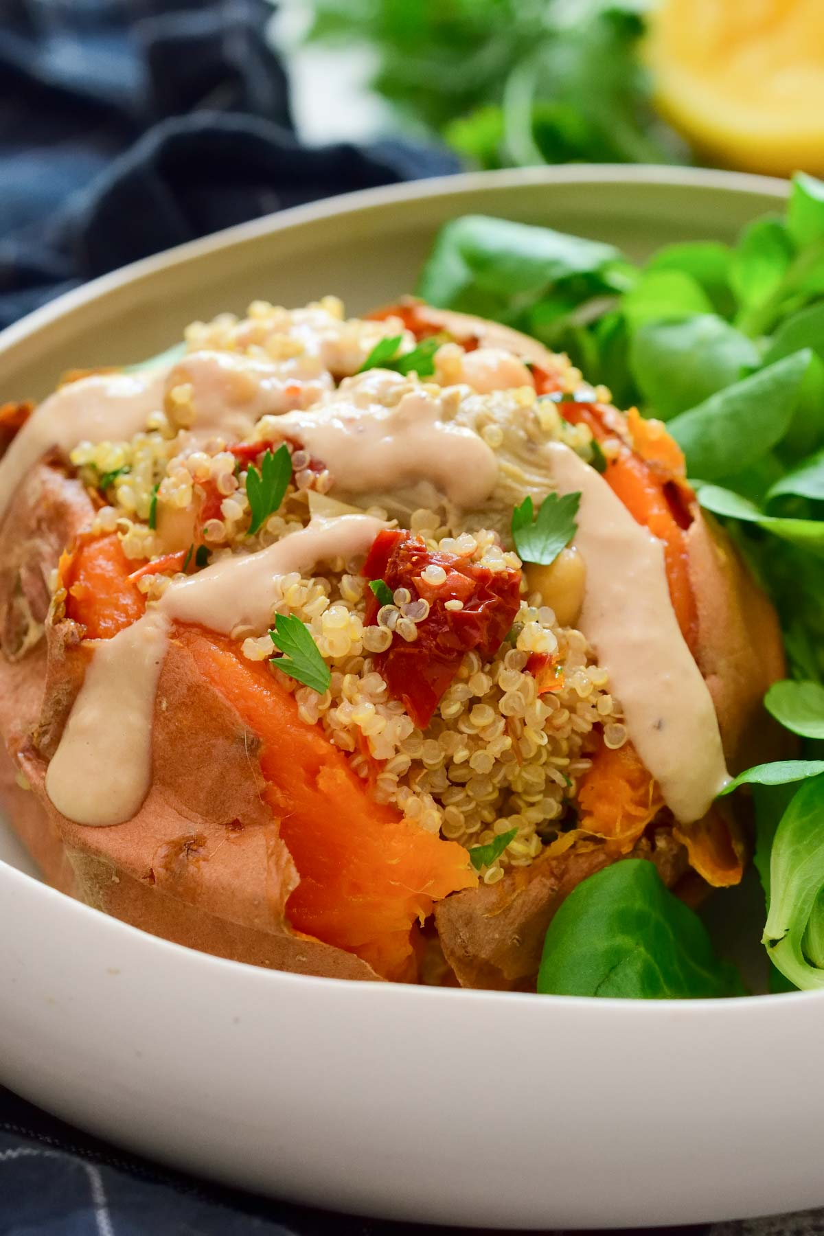 A close-up image of a quinoa-stuffed sweet potato with hummus sauce on top. Green salad in the background.