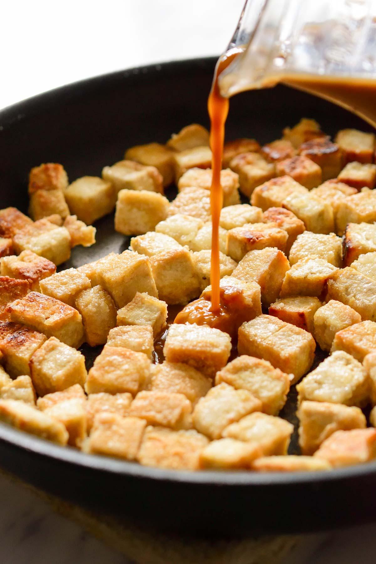 Pouring the teriyaki sauce into the pan of crispy fried tofu.