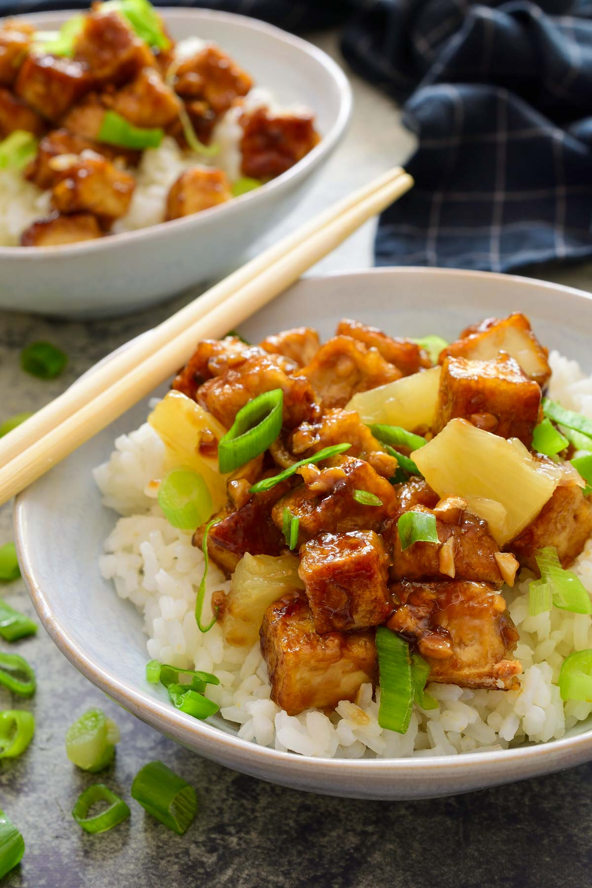 A white bowl of teriyaki tofu with pineapple over rice. Two chopsticks on the side of the bowl.