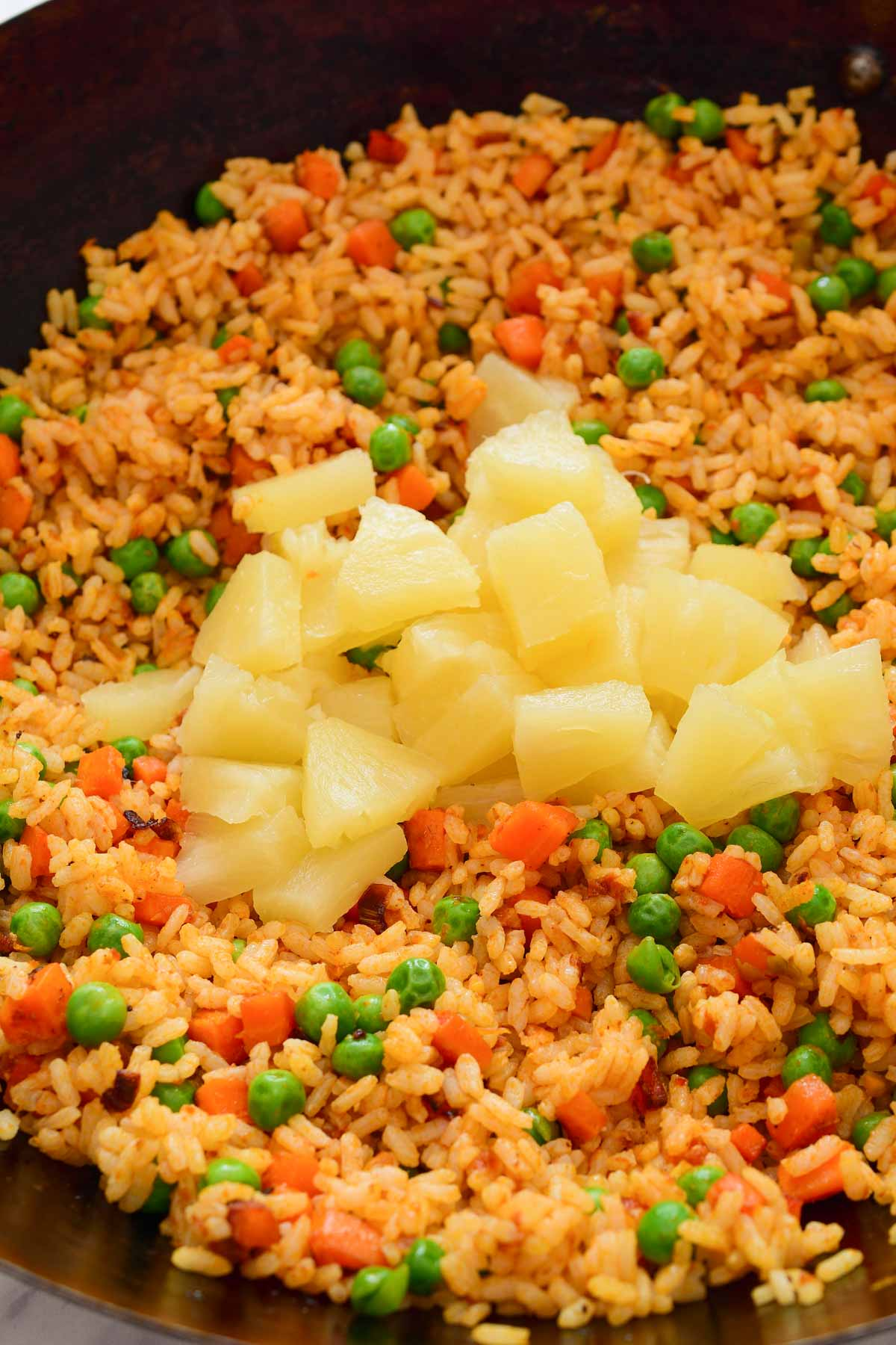 A wok filled with fried rice with a pile of chopped pineapple on top.
